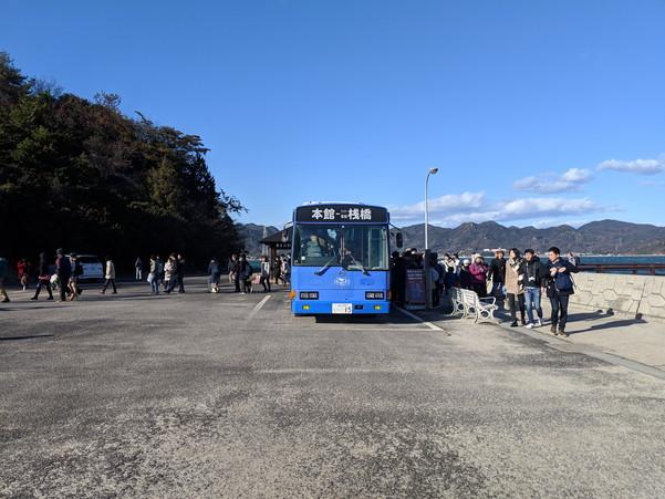 大久野島の港で無料送迎バスに乗る観光客